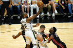 Milwaukee Bucks forward Khris Middleton (22) shoots over Miami Heat center Bam Adebayo (13) during the second half of Game 4 of an NBA basketball first-round playoff series, Saturday, May 29, 2021, in Miami. (AP Photo/Lynne Sladky)
