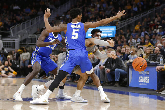 Marquette's Markus Howard passes out of a double-team by Creighton's Ty-Shon Alexander (5) and Damien Jefferson (23) during the first half of an NCAA college basketball game Tuesday, Feb. 18, 2020, in Milwaukee. (AP Photo/Aaron Gash)