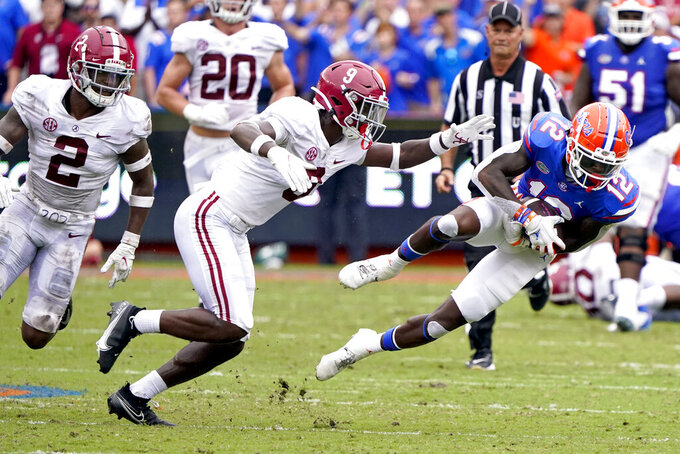 Florida wide receiver Rick Wells (12) is stopped by Alabama defensive back Jordan Battle (9) after a reception for a first down during the first half of an NCAA college football game, Saturday, Sept. 18, 2021, in Gainesville, Fla. (AP Photo/John Raoux)