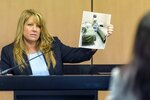 FILE- In this April 30, 2019, file pool photo, Karen Herzog, a Florida Department of Health inspector, shows a photo she took of beds in a room during her inspection of Orchids of Asia Day Spa, during a motion hearing in the Robert Kraft prostitution solicitation case in West Palm Beach, Fla. Florida prosecutors will try to save their prostitution solicitation case against New England Patriots owner Kraft when they argue before an appellate court Tuesday, June 30, 2020, that his rights weren't violated when police secretly video recorded him allegedly paying for sex at a massage parlor. (Lannis Waters/The Palm Beach Post via AP, Pool, File)