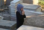 A woman prays near the grave of her relative during the first day of Eid al-Fitr in Ghazali cemetery, Baghdad, Iraq, Friday, June 15, 2018. Eid al-Fitr marks the end of the Muslims' holy month of Ramadan. (AP Photo/Hadi Mizban)
