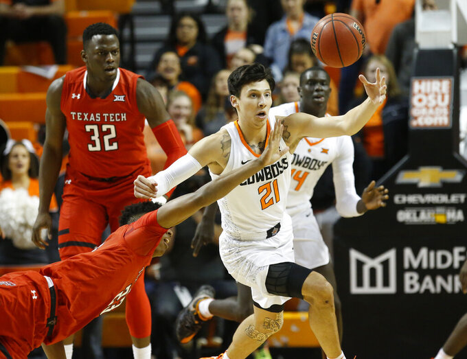 FILE - In this Feb. 13, 2019, file photo, Texas Tech guard Jarrett Culver, left, and Oklahoma State guard Lindy Waters III (21) reach for the ball in the first half of an NCAA college basketball game in Stillwater, Okla. The Cowboys have a trio of senior captains who are primed to lead the Cowboys back to prominence - Lindy Waters III, Cameron McGriff and Thomas Dziagwa. (AP Photo/Sue Ogrocki, File)