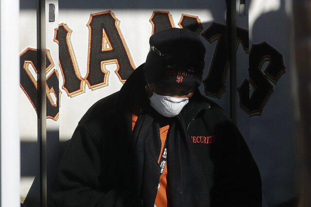 Security guard LeJuana Evans wears a mask while working a gate at Oracle Park, the San Francisco Giants' baseball ballpark, in San Francisco, March 26, 2020. (AP Photo/Jeff Chiu)