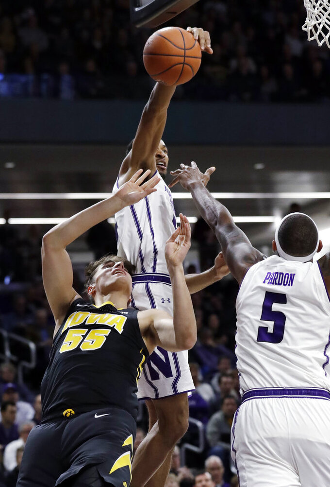 Northwestern guard Ryan Taylor, top, blocks a shot by Iowa forward Luka Garza (55) during the first half of an NCAA college basketball game Wednesday, Jan. 9, 2019, in Evanston, Ill. (AP Photo/Nam Y. Huh)