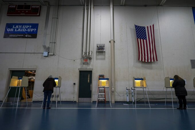 FILE- In this Nov. 3, 2020, file photo people vote at the Milwaukee County Sports Complex in Franklin, Wis. The Wisconsin Supreme Court sided with Democrats on Friday, April 9, 2020, and ruled that the state elections commission should not remove from the rolls voters flagged as possibly having moved, something conservatives have wanted done for nearly two years. (AP Photo/Morry Gash)