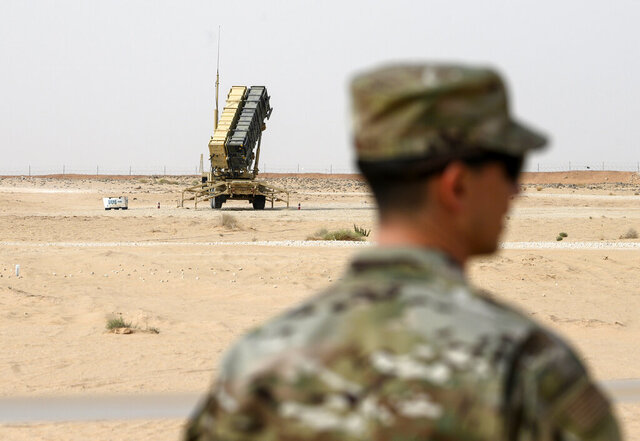 FILE - In this Feb. 20, 2020, file photo, a member of the U.S. Air Force stands near a Patriot missile battery at the Prince Sultan air base in al-Kharj, central Saudi Arabia. The U.S. is pulling two Patriot missile batteries and some fighter aircraft out of Saudi Arabia, an American official said Thursday, May 7, amid tensions between the kingdom and the Trump administration over oil production. (Andrew Caballero-Reynolds/Pool via AP, File)