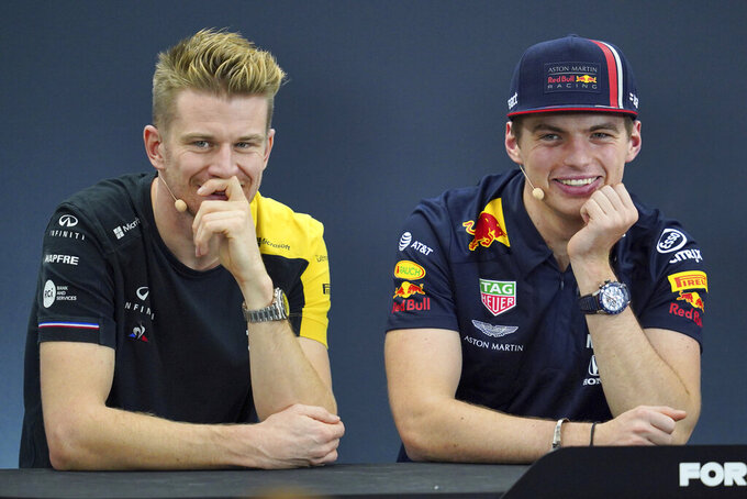 Renault driver Nico Hulkenberg, left, of Germany and Red Bull driver Max Verstappen of the Netherlands listen to a reporter's questions during a press conference for the Japanese Formula One Grand Prix at Suzuka Circuit in Suzuka, Thursday, Oct. 10, 2019. (AP Photo/Toru Hanai)
