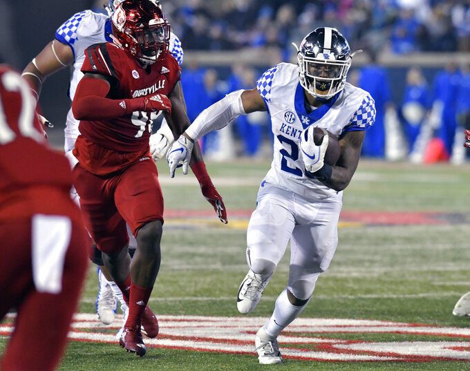 Kentucky running back Benny Snell Jr. (26) runs through an opening in the Louisville defensive line during the first half of an NCAA college football game in Louisville, Ky., Saturday, Nov. 24, 2018. (AP Photo/Timothy D. Easley)