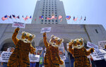 FILE - In this July 7, 2016, file photo, led by three costumed tigers, dozens of animal rights protesters with People for the Ethical Treatment of Animals (PETA) gather at City Hall in Los Angeles to call on the city to prohibit using tigers, lions, and other wild animals in circuses.  California will be the first state to ban the sale and manufacture of new fur products and the third to bar most animals from circus performances under a pair of bills signed Saturday, Oct. 12, 2019 by Gov. Gavin Newsom.  (AP Photo/Richard Vogel, File)