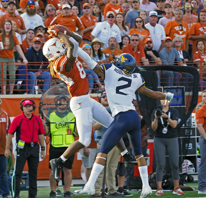 Texas receiver Lll'Jordan Humphrey, left, catches a pass against West Virginia defender Kenny Robinson, Jr. during the second half of an NCAA college football game, Saturday, Nov. 3, 2018, in Austin, Texas. West Virginia won 42-41. (AP Photo/Michael Thomas)