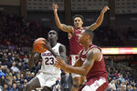 Connecticut's Akok Akok, left, looks to shoot as Temple's Nate Pierre-Louis, top, and Temple's J.P. Moorman II, right, defend in the second half of an NCAA college basketball game, Wednesday, Jan. 29, 2020, in Storrs, Conn. (AP Photo/Jessica Hill)