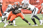 Cleveland Browns defensive end Myles Garrett (95) runs around Las Vegas Raiders tight end Darren Waller (83) during the first half of an NFL football game, Sunday, Nov. 1, 2020, in Cleveland. Garrett injured his knee in the first quarter in the Browns 16-6 loss to the Raiders. (AP Photo/David Richard)