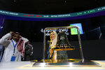 Saudi Arabia's state-owned oil company employee Sukaynah Al Oqaili rings the stock bell as she celebrates during the official ceremony marking the debut of Aramco's initial public offering (IPO) on the Riyadh's stock market in Riyadh, Saudi Arabia, Wednesday, Dec. 11, 2019. (AP Photo/Amr Nabil)