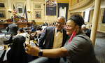 """Del. Luke Torian, D-Prince William, left, and Del. Cia Price, D-Newport News, right, pose for a """"selfie"""" during a break in the House of Delegates floor session inside the Virginia State Capitol in Richmond, Va., Monday, Aug. 2, 2021, the first day of the General Assembly Special Session. (Bob Brown/Richmond Times-Dispatch via AP)"""