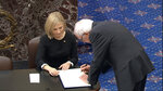 In this image from video, Sen. Bernie Sanders, I-Vt., signs the oath book after being sworn in for the impeachment trial of President Donald Trump in the Senate at the U.S. Capitol in Washington, Thursday, Jan. 16, 2020. (Senate Television via AP)