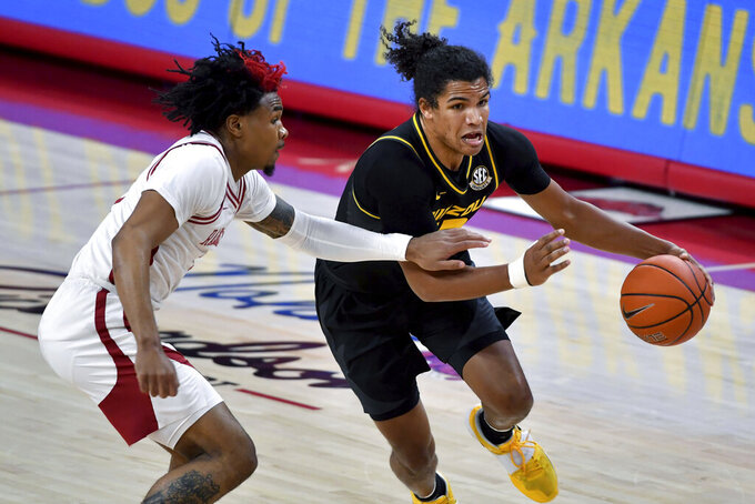Missouri guard Dru Smith (12) drives past Arkansas defender Desi Sills (3) during the first half of an NCAA college basketball game in Fayetteville, Ark. Saturday, Jan. 2, 2021. (AP Photo/Michael Woods)
