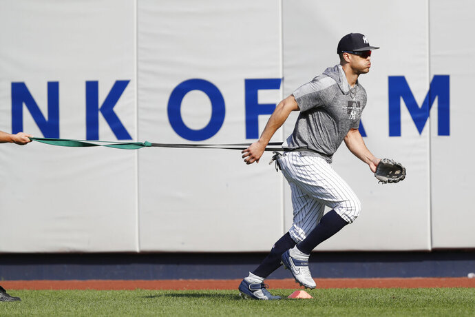 New York Yankees' Giancarlo Stanton, who has been out the much of the season with various injuries, trains with a resistance band in the outfield before a baseball game between the Yankees and the Texas Rangers, Wednesday, Sept. 4, 2019, in New York. (AP Photo/Kathy Willens)