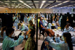 Health workers take swab samples collection for a Covid-19 antigen test ahead of the Cruilla music festival in Barcelona, Spain, Friday, July 9, 2021. (AP Photo/Joan Mateu)