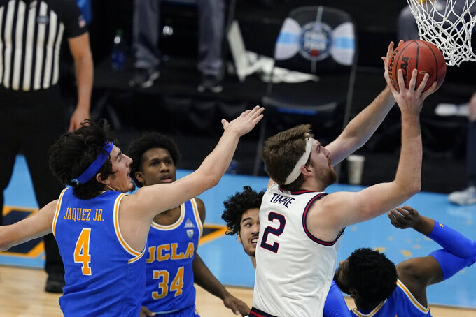 Gonzaga forward Drew Timme (2) drives to the basket past UCLA guard Jaime Jaquez Jr. (4) during the first half of a men's Final Four NCAA college basketball tournament semifinal game, Saturday, April 3, 2021, at Lucas Oil Stadium in Indianapolis. (AP Photo/Darron Cummings)