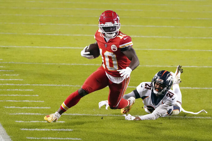 FILE - Kansas City Chiefs wide receiver Tyreek Hill (10) runs past Denver Broncos cornerback A.J. Bouye (21) in the first half of an NFL football game in Kansas City, Mo., in this Sunday, Dec. 6, 2020, file photo. Hill was selected Friday, Jan. 8, 2021, to The Associated Press All-Pro Team. (AP Photo/Charlie Riedel, File)
