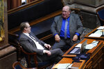 Rep. Dave Deyoe, R-Nevada, left, talks with Rep. Gary Worthan, R-Storm Lake, right, during the opening day of the Iowa Legislature, Monday, Jan. 11, 2021, at the Statehouse in Des Moines, Iowa. (AP Photo/Charlie Neibergall)