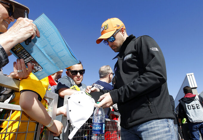 Driver Ricky Stenhouse Jr. signs autographs for fans prior to the start of the NASCAR Cup Series auto race at ISM Raceway, Sunday, March 10, 2019, in Avondale, Ariz. (AP Photo/Ralph Freso)