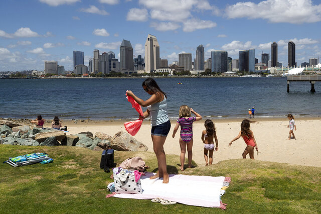 A family set up at a beach looking out towards the San Diego skyline Tuesday, May 19, 2020, in Coronado, Calif. With encouraging results in their fight against the coronavirus, San Diego County supervisors voted Tuesday to ask the state to allow California's second-largest county to be a test case for whether more rapid reopening can safely occur.(AP Photo/Gregory Bull)