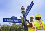 Richmond employees Andre Cannady, left, and Silas Poindexter install an Arthur Ashe Boulevard sign at the intersection with Kensington Avenue in Richmond, Va., Saturday, June 22, 2019. Groundbreaking black tennis player Arthur Ashe Jr.'s hometown of Richmond has renamed a major thoroughfare after him, after years of effort. (Alexa Welch Edlund/Richmond Times-Dispatch via AP)
