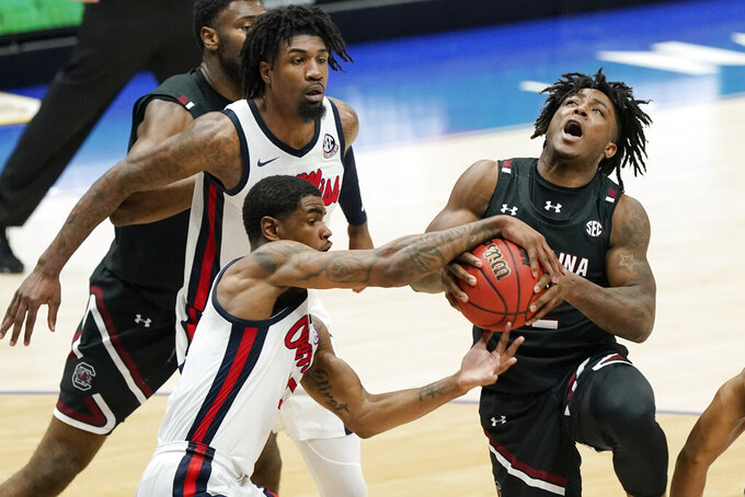 Mississippi's Luis Rodriguez, lower left, gets his hands on the ball as South Carolina's Trae Hannibal (12) drives to the basket in the second half of an NCAA college basketball game in the Southeastern Conference Tournament Thursday, March 11, 2021, in Nashville, Tenn. (AP Photo/Mark Humphrey)