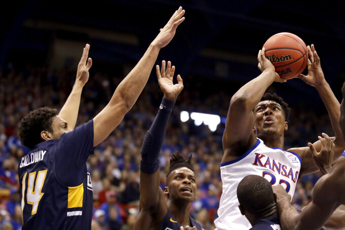 Kansas' David McCormack, right, shoots next to UNC Greensboro's Kyrin Galloway (14) during the first half of an NCAA college basketball game Friday, Nov. 8, 2019, in Lawrence, Kan. (AP Photo/Charlie Riedel)
