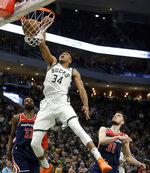 Milwaukee Bucks' Giannis Antetokounmpo (34) dunks against Washington Wizards' Jeff Green (32) and Tomas Satoransky (31) during the second half of an NBA basketball game Wednesday, Feb. 6, 2019, in Milwaukee. (AP Photo/Aaron Gash)