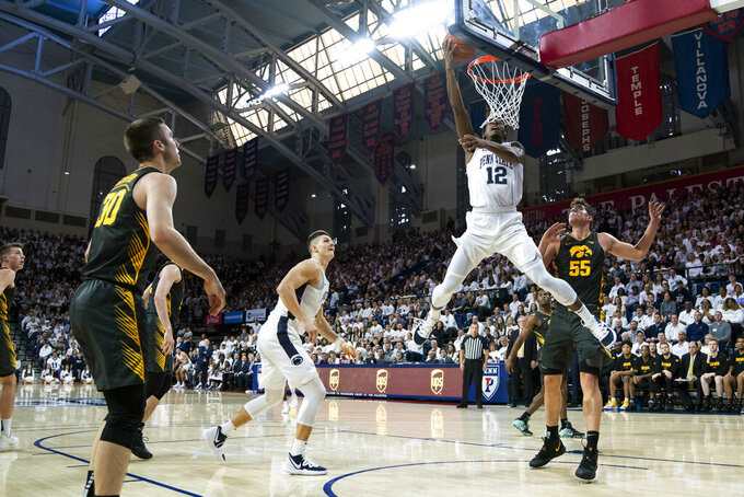 Penn State's Izaiah Brockington, center, goes up for the shot with Iowa's Luka Garza, right, defending during the first half of an NCAA college basketball game Saturday, Jan. 4, 2020, in Philadelphia. (AP Photo/Chris Szagola)