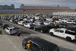 Cars full of graduates and their families line up before a drive-thru graduation for Faith Lutheran High School at the Las Vegas Motor Speedway, Friday, May 22, 2020, in Las Vegas. The school held a special drive-thru graduation amid the coronavirus pandemic. (AP Photo/John Locher)