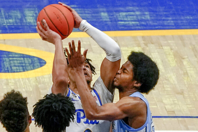 Pittsburgh's Ithiel Horton, left, shoots as North Carolina's Kerwin Walton defends during the second half of an NCAA college basketball game Tuesday, Jan. 26, 2021, in Pittsburgh. North Carolina won 75-65. (AP Photo/Keith Srakocic)