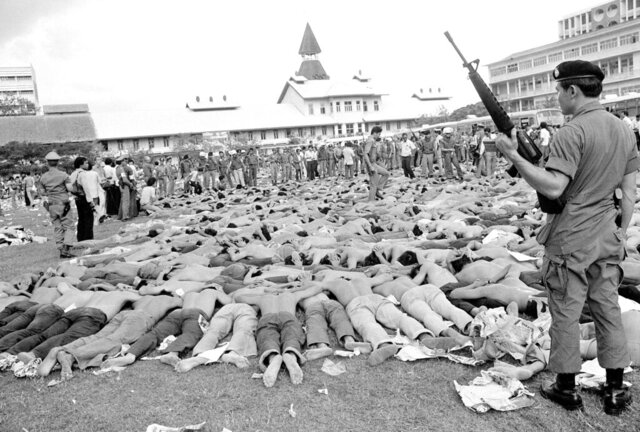 FILE - In this Oct. 6, 1976, file photo, police stand guard over leftist Thai students on a soccer field at Thammasat University, in Bangkok, Thailand. This year's anti-government protests are seeking new elections, a more democratic constitution and an end to intimidation of political activists. Their speeches have repeatedly highlighted the 1976 tragedy, piquing the interest of the current generation in what their forebears faced. (AP Photo/Gary Mangkorn, File)
