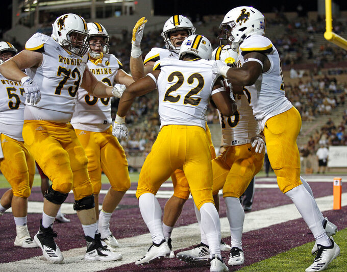 Wyoming running back Nico Evans (22) is congratulated by teammates after his touchdown against New Mexico State in the first half of an NCAA college football game in Las Cruces, N.M., Saturday, Aug. 25, 2018. (AP Photo/Andres Leighton)