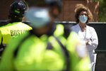 A doctor from Massachusetts General Hospital stands in counter-protest across the street from a demonstration calling for the lifting of all government restrictions related to concern about the spread of COVID-19, Saturday, May 30, 2020, outside the Statehouse in Boston. (AP Photo/Michael Dwyer)