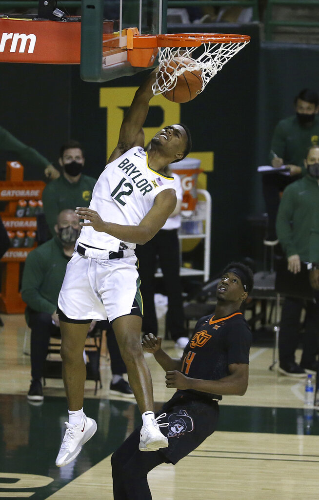 Baylor guard Jared Butler (12) dunks the ball past Oklahoma State guard Bryce Williams (14) in the second half of an NCAA college basketball game, Thursday, March 4, 2021, in Waco, Texas. (AP Photo/Jerry Larson)