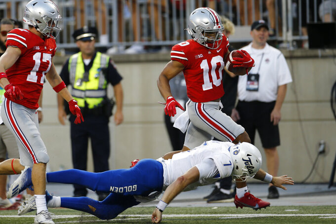 Ohio State defensive back Cameron Martinez, top right, runs over Tulsa quarterback Davis Brin, bottom, to score a touchdown after an interception during the second half of an NCAA college football game Saturday, Sept. 18, 2021, in Columbus, Ohio. (AP Photo/Jay LaPrete)