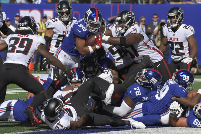 New York Giants running back Saquon Barkley (26) pushes through a scrum for a touchdown during the second half of an NFL football game against the Atlanta Falcons, Sunday, Sept. 26, 2021, in East Rutherford, N.J. (AP Photo/Bill Kostroun)