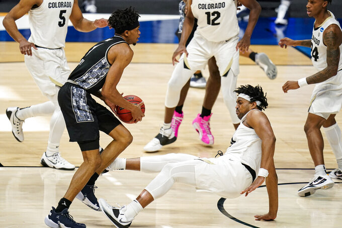 Colorado forward Evan Battey, right, draws the charge from Georgetown forward Jamorko Pickett in the second half of a first-round game in the NCAA men's college basketball tournament at Hinkle Fieldhouse in Indianapolis, Saturday, March 20, 2021. (AP Photo/Michael Conroy)