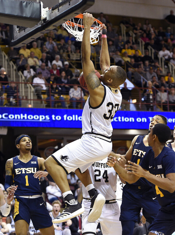 Wofford forward Cameron Jackson (33) dunks over East Tennessee State guard Tray Boyd III (1), forward Jeromy Rodriguez (11) and guard Daivien Williamson (4) in the second half of a semifinal NCAA college basketball game for the Southern Conference tournament championship, Sunday, March 10, 2019, in Asheville, N.C. (AP Photo/Kathy Kmonicek)