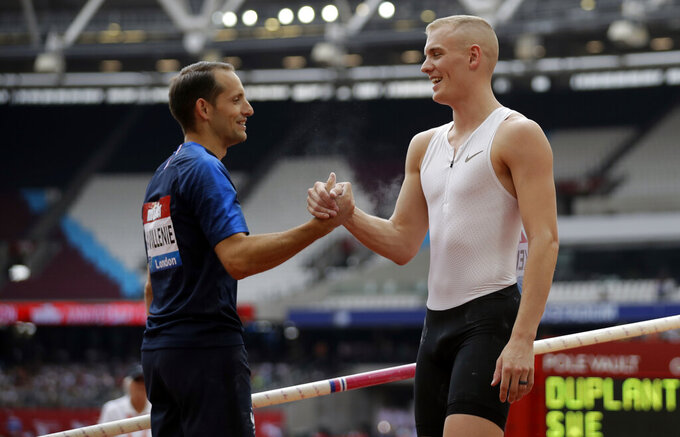 """FLE - In this July 21, 2018, file photo, second placed Renaud Lavillenie of France, left, shakes hands with winner Sam Kendricks at the men's pole vault event at the IAAF Diamond League athletics meeting in London. The three biggest names in men's pole vault will compete against each other from their own backyards, Sunday, May 3, 2020, in a rare sporting event during the coronavirus pandemic. Video links will connect world record holder Mondo Duplantis, world champion Sam Kendricks and former Olympic champion Renaud Lavillenie. World Athletics calls it """"The Ultimate Garden Clash"""" and will stream it on social media. (AP Photo/Matt Dunham, File)"""