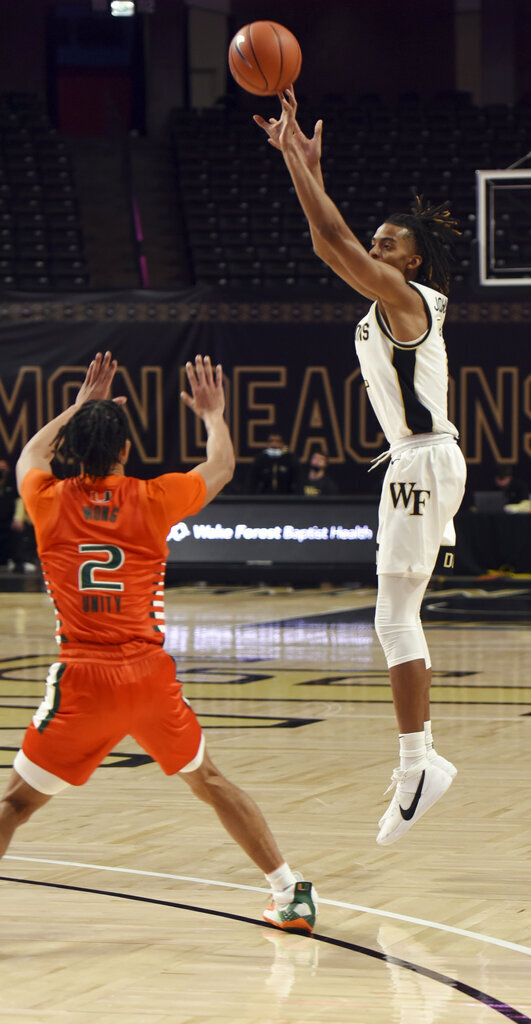 CORRECTS ID TO MIAMI'S ISAIAH WONG, NOT MIAMI'S DONALD CHANEY JR. Wake Forest's Jalen Johnson shoots from 3-point range under pressure from Miami's Isaiah Wong during an NCAA college basketball game, Saturday, Jan. 30, 2021, at Joel Coliseum in Winston-Salem, N.C. (Walt Unks/The Winston-Salem Journal via AP)