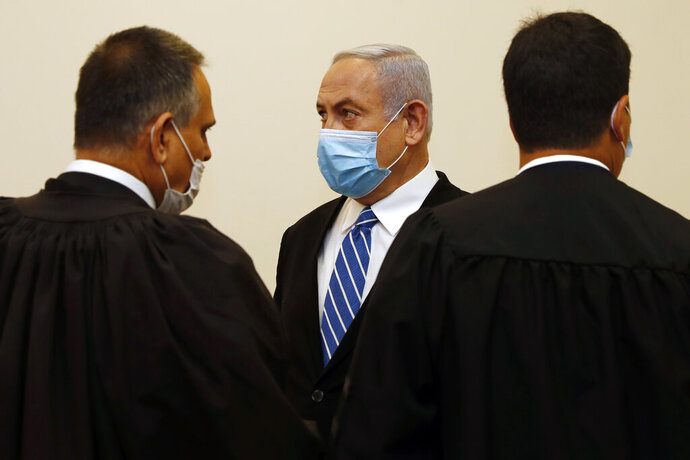 Israeli Prime Minister Benjamin Netanyahu, center, wearing a face mask in line with public health restrictions due to the coronavirus pandemic, stands with his lawyers inside the court room as his corruption trial opens at the Jerusalem District Court, Sunday, May 24, 2020. He is the country's first sitting prime minister ever to go on trial, facing charges of fraud, breach of trust, and accepting bribes in a series of corruption cases stemming from ties to wealthy friends. (Ronen Zvulun/ Pool Photo via AP)