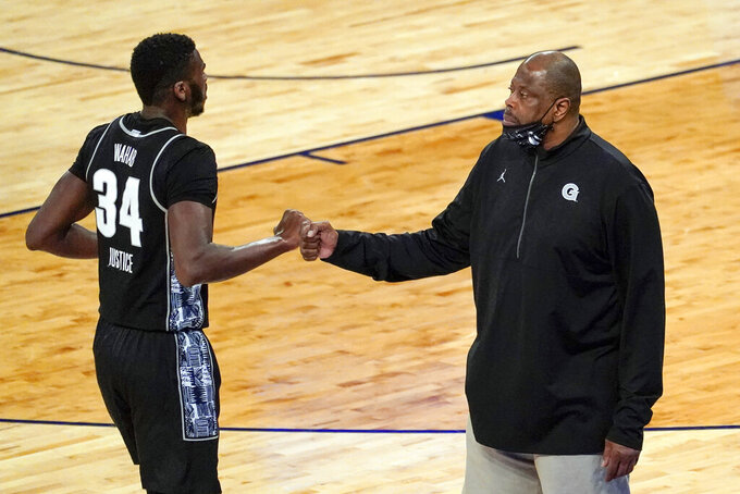 Georgetown center Qudus Wahab (34) fists bumps head coach Patrick Ewing during the first half of an NCAA college basketball game against Villanova in the quarterfinals of the Big East conference tournament, Thursday, March 11, 2021, in New York. (AP Photo/Mary Altaffer)