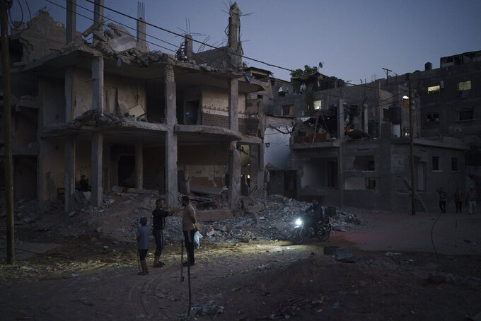 A man rides his motorcycle at night on Al-Baali Street as Palestinians stand next to homes heavily damaged by airstrikes in Beit Hanoun, northern Gaza Strip, Friday, June 11, 2021. (AP Photo/Felipe Dana)