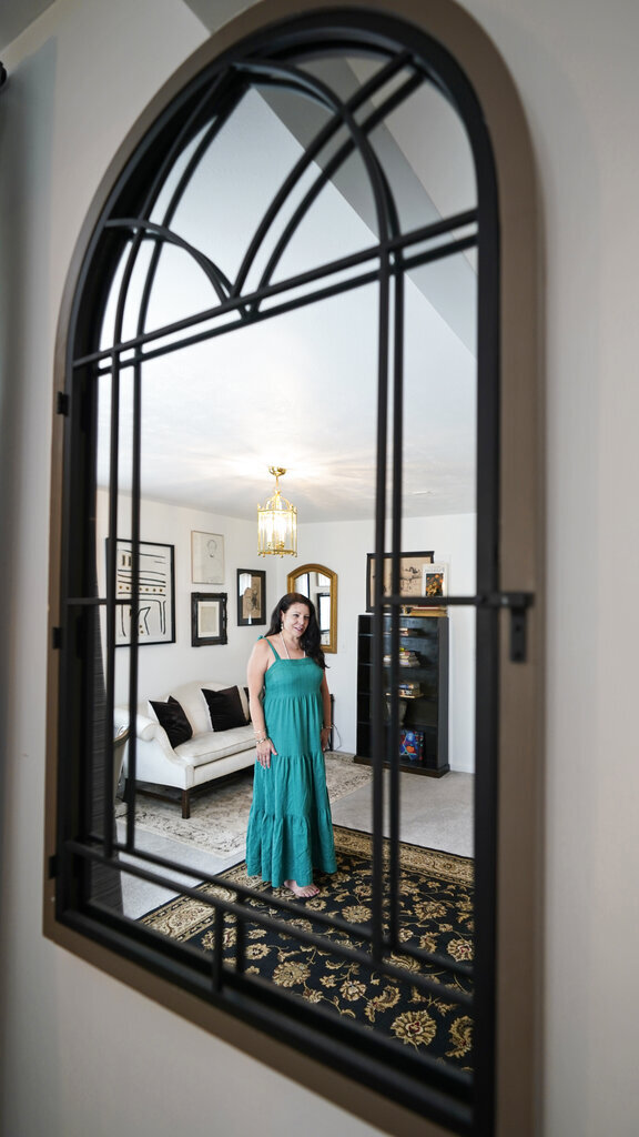 """Heather Bise, owner of The House of Bise Bespoke, is reflected in a mirror in the """"Art"""" bedroom, Monday, July 19, 2021, in Cleveland. Small businesses in the U.S. that depend on tourism and vacationers say business is bouncing back, as people re-book postponed trips and take advantage of loosening restrictions, a positive sign for the businesses that have struggled for more than a year. Bise started in 2019 and catered to international tourists, attracting guests from New Zealand, Botswana, Eastern Europe and elsewhere. (AP Photo/Tony Dejak)"""