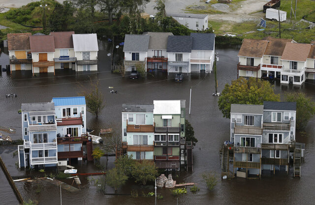 FILE - In a Sunday, Sept. 16, 2018 photo, homes along the New River are flooded as a result of high tides and rain from hurricane Florence which moved through the area in Jacksonville, N.C. As hurricane season starts Monday, May 31, 2020, most of North Carolina's coastal counties are grappling with shortfalls or concerns about equipment and resources as they balance the dual threat of tropical weather and the COVID-19 pandemic. All 20 counties in the state's coastal management zone told the Associated Press that COVID-19 is factoring into hurricane preparations. (AP Photo/Steve Helber, File)