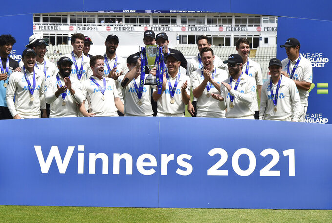 New Zealand players celebrate with the winners trophy after their win in the second cricket test match between England and New Zealand at Edgbaston in Birmingham, England, Sunday, June 13, 2021. New Zealand won the series 1-0. (AP Photo/Rui Vieira)